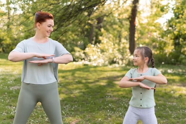 Tiro medio niña y mujer haciendo ejercicio juntos