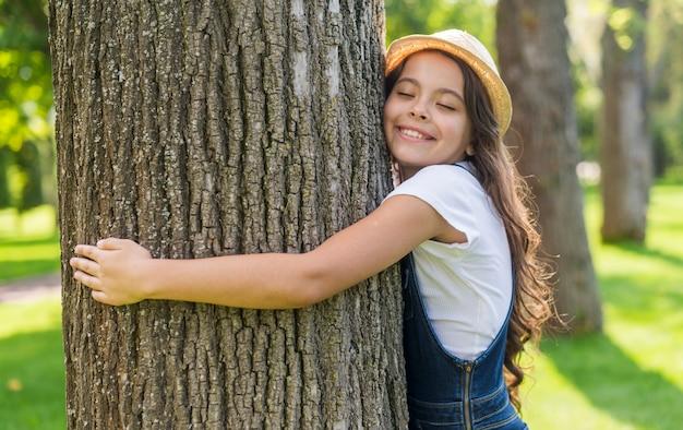 Tiro medio niña sonriente abrazando un árbol