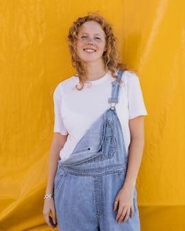 Tiro medio niña sonriente con fondo amarillo