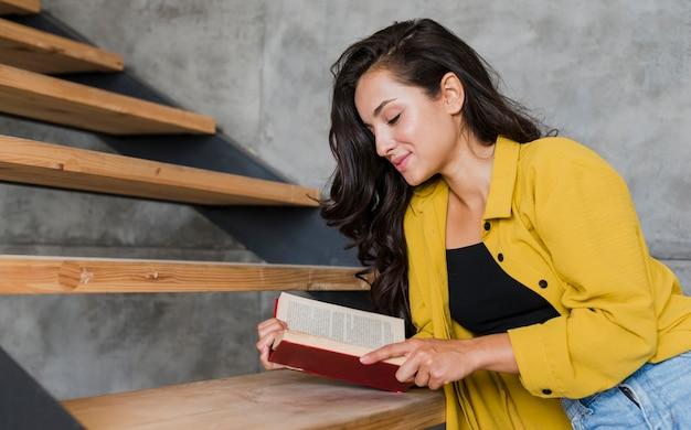 Tiro medio niña sonriente con libro en las escaleras