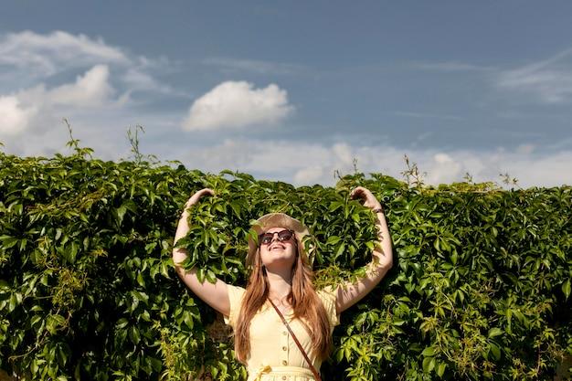 Tiro medio niña sonriente posando al aire libre