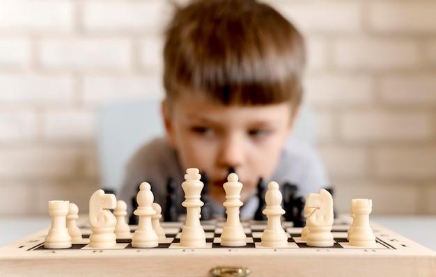 Tiro medio niño borroso con juego de ajedrez