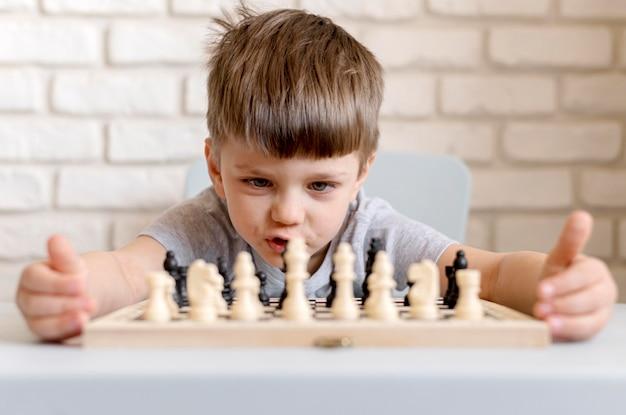 Tiro medio niño jugando al ajedrez