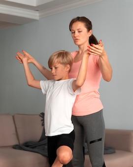 Tiro medio niño y mujer meditando