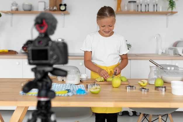 Tiro medio niño sonriente cortando manzanas