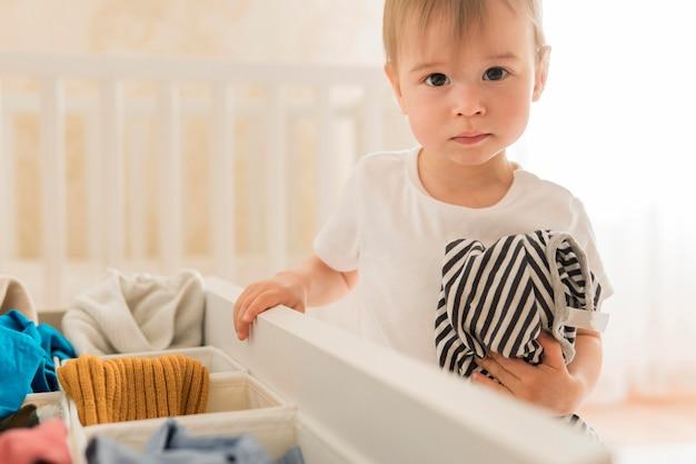 Tiro medio niño tomando ropa del cajón