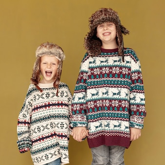 Tiro medio niños felices posando en interiores