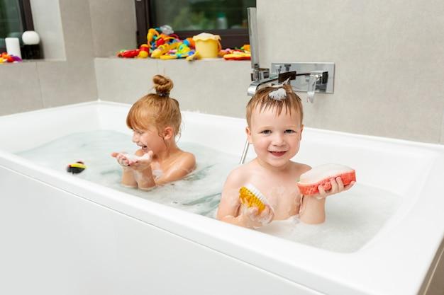 Tiro medio niños pequeños en la bañera
