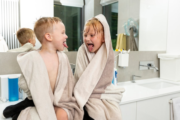 Tiro medio a niños sentados en el baño