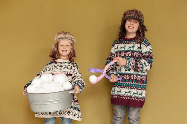 Tiro medio niños sonrientes con bolas de nieve