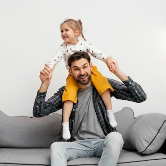 Tiro medio padre sosteniendo a niña sobre los hombros
