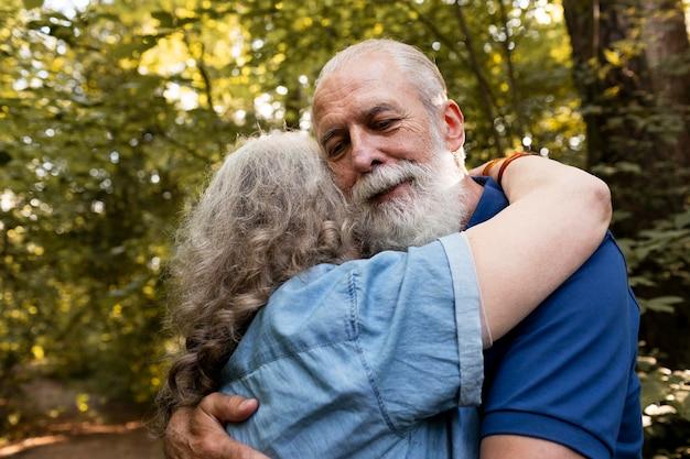 Tiro medio pareja de ancianos abrazándose en la naturaleza