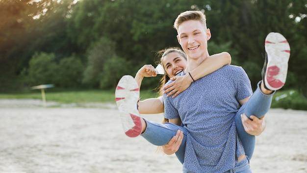 Tiro medio pareja sonriente divirtiéndose en la naturaleza
