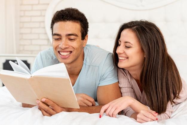 Tiro medio pareja sonriente leyendo en la cama