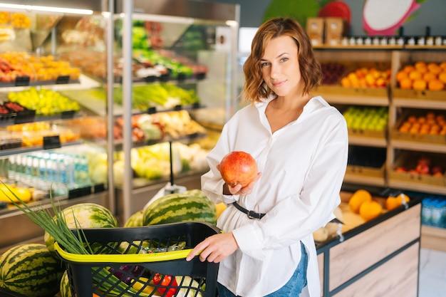Tiro medio retrato de atractiva joven sosteniendo granada de pie con canasta de frutas