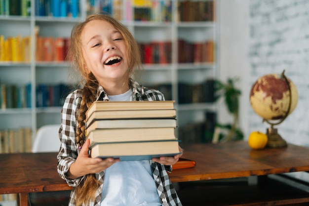 Tiro medio retrato de niña de la escuela primaria riendo sosteniendo la pila de libros en la biblioteca en