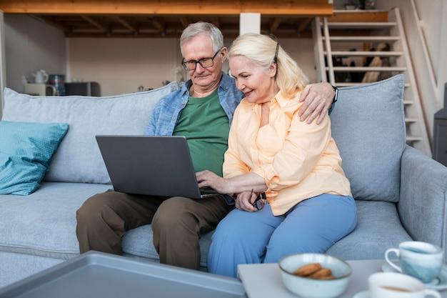 Tiro medio sonriente pareja de jubilados con portátil