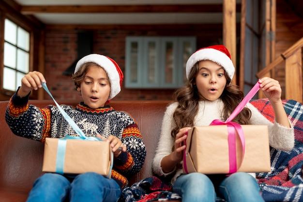 Tiro medio sorprendido hermano y hermana abriendo regalos