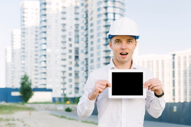 Tiro medio sorprendido hombre sosteniendo tableta