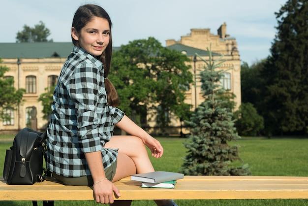 Tiro medio de la vista lateral de la muchacha del highschool que se sienta en banco