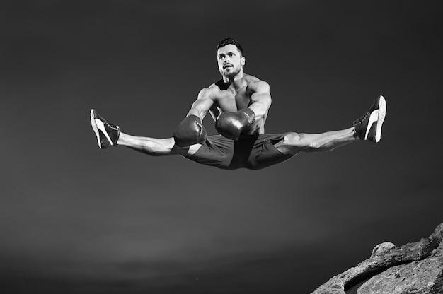 Tiro monocromo de un apuesto joven gimnasta masculino saltando alto haciendo divisiones en el aire copyspace deportes fitness estilo de vida estiramiento flexible piernas actividad energética gimnasia salto concepto de mosca.