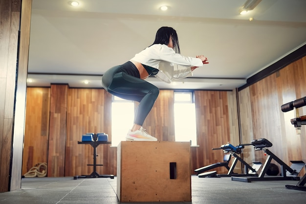 Tiro de la mujer joven que se resuelve con una caja en el gimnasio. atleta femenina cuadro saltando en un gimnasio de entrenamiento funcional