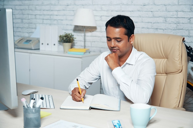 Tiro en el pecho del trabajador de cuello blanco sentado en el escritorio de la oficina y tomando notas