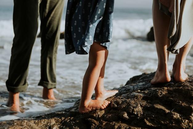 Un tiro de pies de personas caminando sobre rocas en la playa