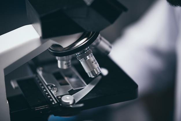 Tiro del primer del microscopio con la lente del metal en el laboratorio.