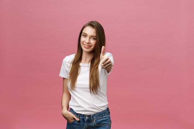 Tiro del primer de la muchacha bonita sonriente que muestra el pulgar encima del gesto.