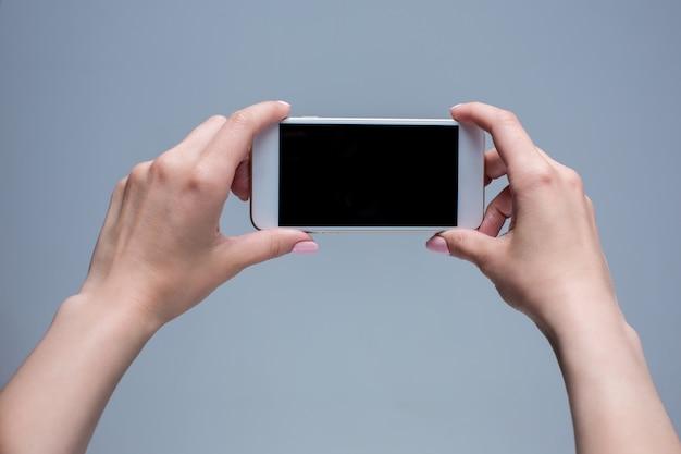 Tiro del primer de una mujer que pulsa en el teléfono móvil en gris.