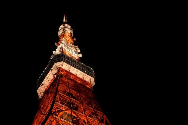 Tiro de primer plano de ángulo bajo de la parte superior de la torre de tokio en japón con un fondo oscuro