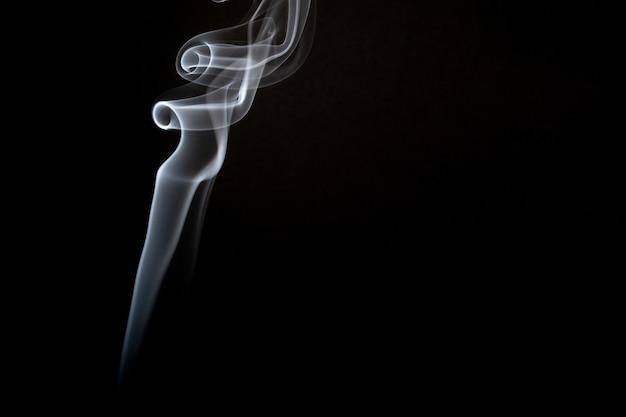 Tiro realista de una voluta de humo sobre un fondo negro