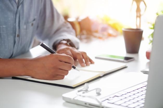 Tiro recortada un hombre escribiendo en un cuaderno sobre el lugar de trabajo.