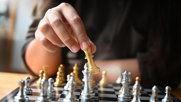 Tiro recortado joven palideciendo tablero de ajedrez en la mesa.