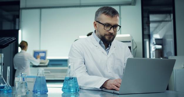 Tiro del retrato del hombre caucásico en los vidrios y el traje blanco que trabaja en la computadora portátil en el laboratorio después con un microscopio.