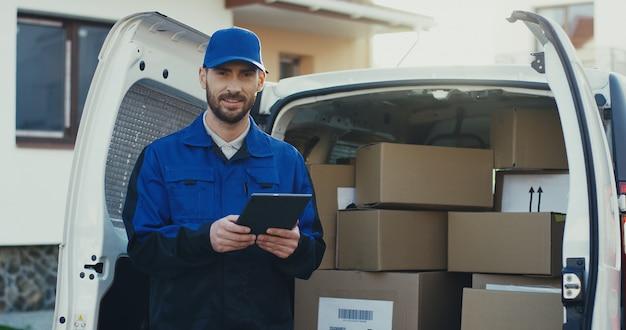 Tiro del retrato del repartidor atractivo caucásico que se coloca en la furgoneta llena de paquetes con una tableta en manos. fuera de.