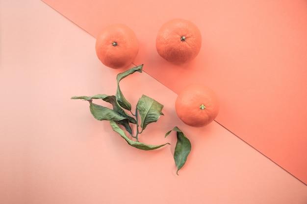 Tiro simétrico de alto ángulo de tres mandarinas frescas y sus hojas verdes sobre fondo naranja