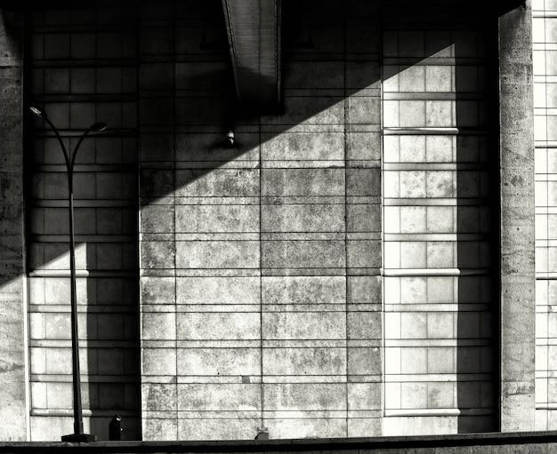 Tiro simétrico en escala de grises de un muro de piedra sombreado - depresión, concepto de soledad