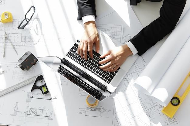 Tiro superior del arquitecto o contratista sentado en el escritorio con computadora portátil, bocetos, casa modelo a escala, rollos de planos y regla, ingresando datos mientras trabaja en un nuevo proyecto de vivienda en su oficina