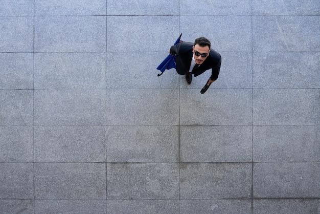 Tiro superior del empresario en traje y gafas de sol de pie sobre el pavimento