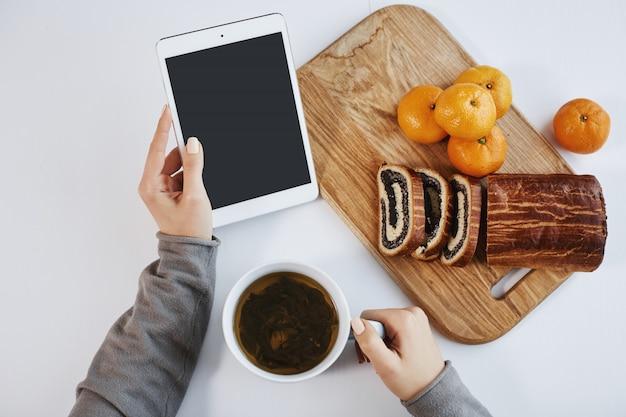 Tiro superior de las manos femeninas que sostienen la tableta digital mientras que desayunando. la mujer inteligente aumenta la energía con una taza de té y come mandarinas con pastel enrollado, sintiéndose genial en la mañana de invierno.