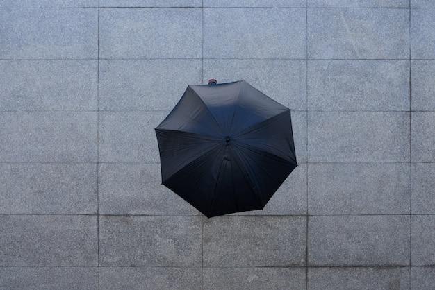 Tiro superior de persona irreconocible de pie bajo el paraguas en el pavimento
