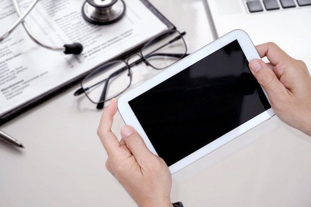 Tiro de la tableta de la tenencia de la mano del doctor con la pantalla negra mientras que trabaja en el hospital.