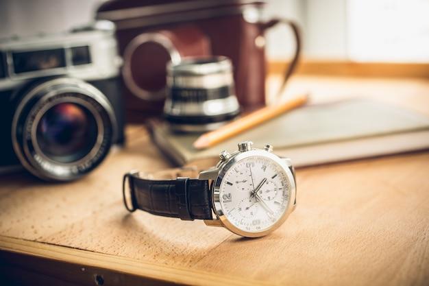 Tiro de tonos de primer plano de relojes masculinos acostado sobre la mesa contra el conjunto retro de fotografía