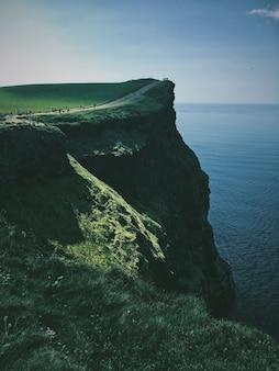 Tiro vertical de un acantilado con un camino en el mar