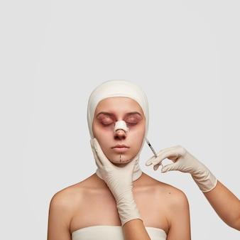 Tiro vertical aislado hembra con hematomas y marcas de elevación, recibe una inyección en la cara antes de la operación plástica