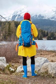 Tiro vertical al aire libre de turista admira el agua turquesa del lago, se para cerca de las rocas, mira montañas nevadas, respira aire fresco, usa sombrero rojo