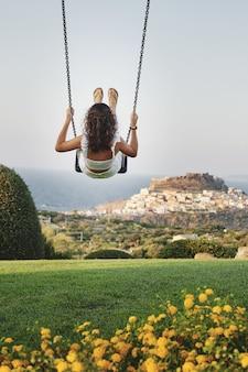 Tiro vertical de alegre mujer balanceándose en un campo de hierba con fondo borroso ideal para blogs