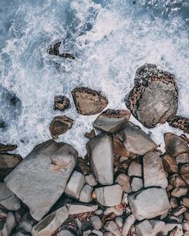 Tiro vertical de alto ángulo de grandes piedras en el agua del océano tormentoso